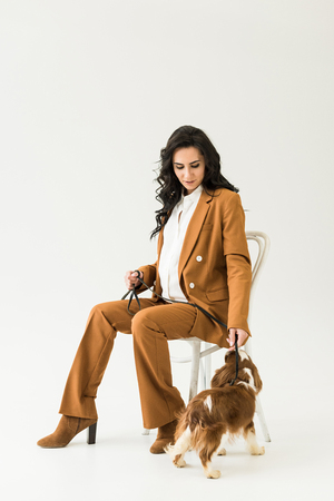 Pregnant woman in brown suit sitting on chair and looking at dog on white background
