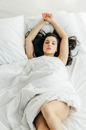 overhead view of attractive brunette woman wrapped in blanket lying on bed Archivio Fotografico - 118998431