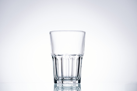 empty glass on white background with backlit and copy space Archivio Fotografico