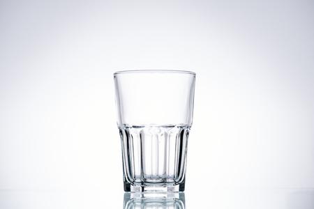 leeres Glas auf weißem Hintergrund mit Hintergrundbeleuchtung und Kopienraum
