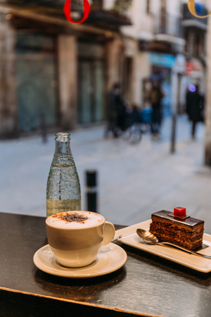 coffee cup, bottle of mineral water and saucer with cake on bar counter, barcelona, spain Stock fotó - 118996693