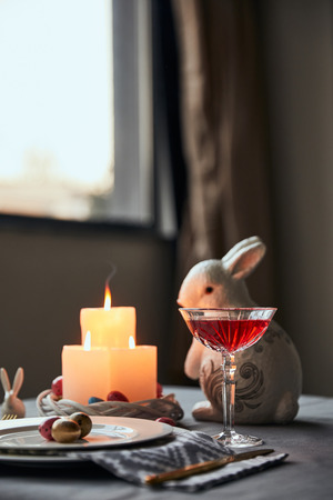 selective focus of plates with eggs, wine in crystal glass and decorative rabbit on table at home
