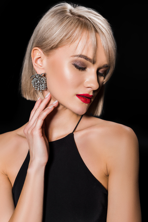 beautiful glamour woman in earrings and black dress, isolated on black Banco de Imagens
