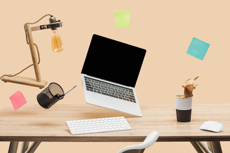 laptop with blank screen, lamp, empty sticky notes and stationery levitating in air above wooden desk with thermomug with coffee splash isolated on beige Standard-Bild - 119043145
