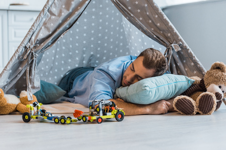 adult man sleeping on pillow in wigwam with toys around Imagens