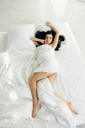 overhead view of brunette woman wrapped in blanket lying on bed