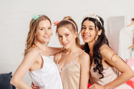 beautiful multicultural girls in headbands and nightwear smiling and looking at camera during pajama party Stock Photo