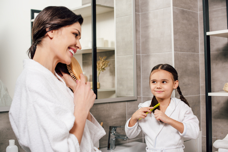 mother and daughter in white bathrobes combing in bathroom Stock fotó