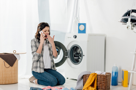 woman sitting near washer, talking on smartphone and yawning in laundry room