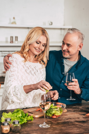 handsome man with glass of wine hugging attractive blonde wife holding green lettuce leaves