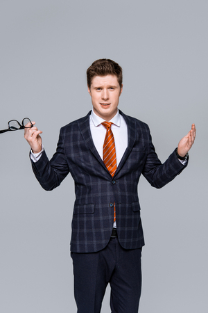 stylish young businessman in suit holding glasses and showing shrug gesture isolated on grey Stock Photo