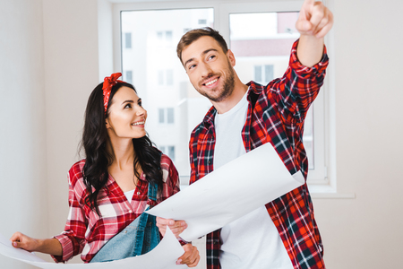 beautiful woman looking at man pointing with finger while holding blueprint at home Standard-Bild - 118995064