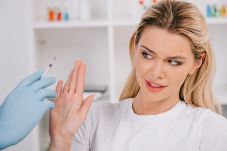 woman gesturing with hand and refusing dentist with local anesthesia syringe