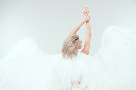 back view of woman with angel wings posing isolated on white with copy space Stock Photo