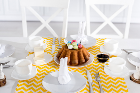 Easter cake with painted eggs and crockery on table 스톡 콘텐츠