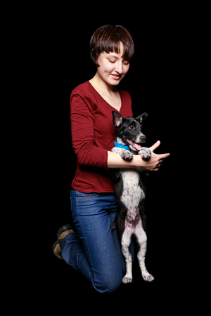 woman in jeans and red sweater with dog in collar on hind legs isolated on black