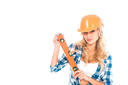 blonde architect woman in blue shirt and orange hardhat with spirit level isolated on white