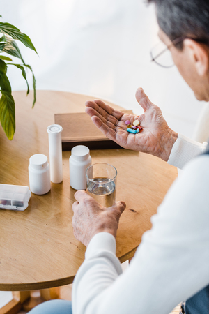 selective focus of retired man looking at pills while holding glass of water Imagens