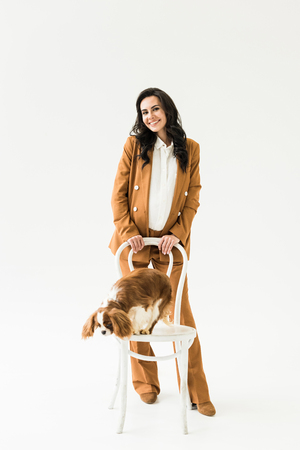 Wonderful pregnant woman in brown suit standing near dog on chair on white background Stock Photo