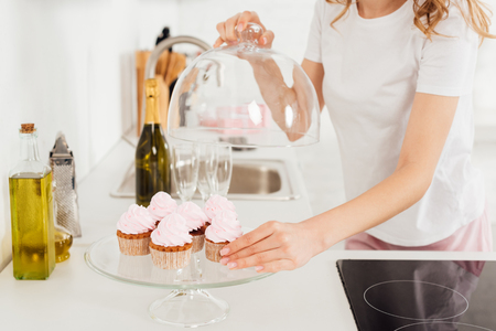 cropped view of girl in pajamas holding dome from glass stand with pink cupcakes in kitchen