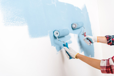 cropped view of man and woman painting wall in blue color at home Standard-Bild - 119044779
