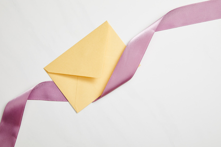 top view of yellow envelope and violet satin ribbon on white