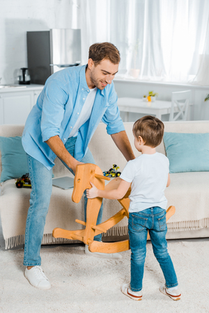 handsome father and preschooler son holding wooden rocking horse at home Фото со стока