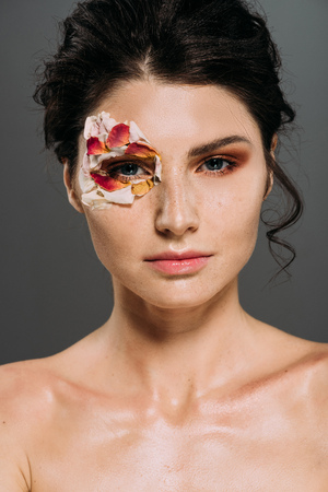 beautiful brunette woman with floral petals around eye isolated on grey
