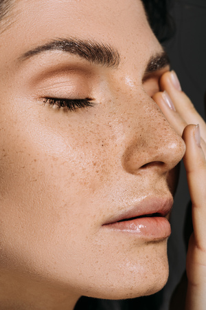close up of beautiful tender woman with freckles on face isolated on grey 写真素材