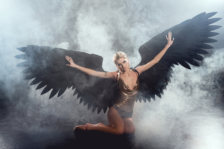 beautiful sexy woman with black angel wings and outstretched hands sitting and posing on dark smoky background