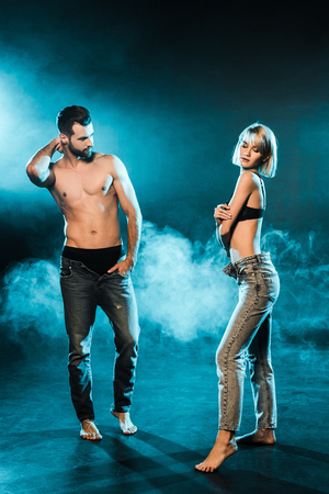 handsome shirtless man and sensual woman posing on blue smoky background 版權商用圖片