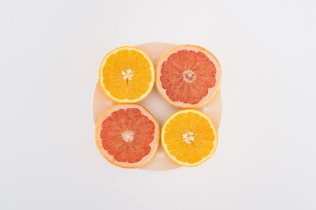 top view of sliced oranges and grapefruits on plate isolated on white