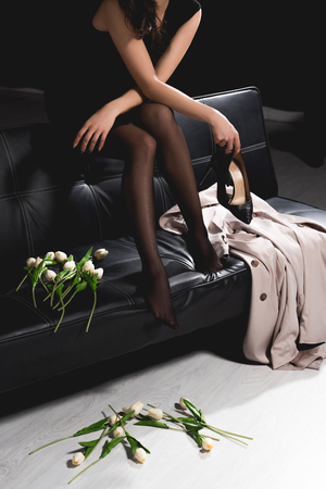 cropped view of woman in black dress sitting on couch and holding white tulips on dark background