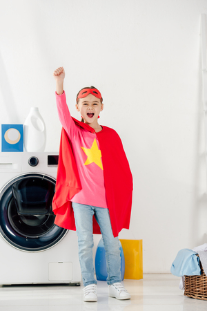 child standing in red homemade suit with star sign and showing celebrating in laundry room