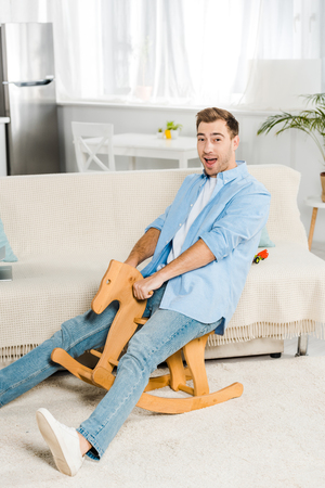 excited handsome man looking at camera and riding wooden rocking horse at home Archivio Fotografico - 118995657