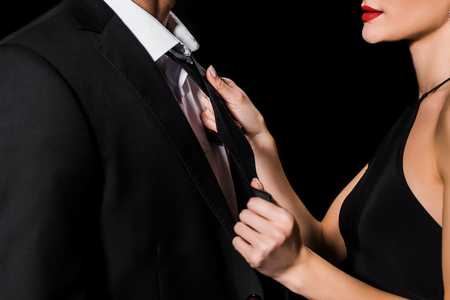 cropped view of glamour couple posing isolated on black
