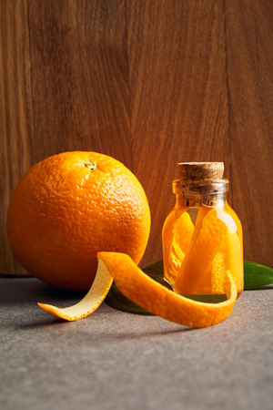 Ripe orange and essential oil in glass bottle on wooden background