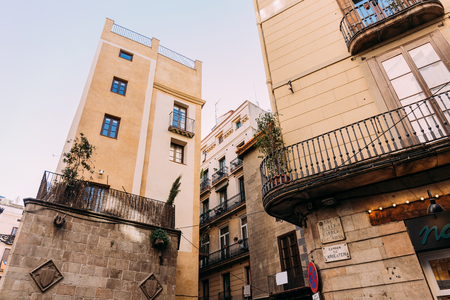 stone houses with balconies on quite street, barcelona, spain