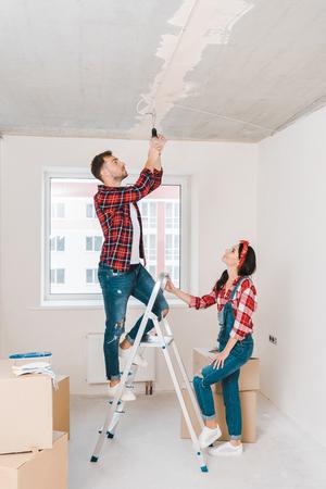 handsome man standing on ladder and changing light bulb near attractive girlfriend Standard-Bild - 118995677