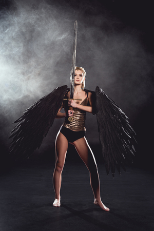 beautiful woman in warrior costume with angel wings holding sword, looking at camera and posing on black smoky background Imagens - 118995688