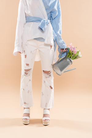 cropped view of young woman holding watering can with flowers and standing in eco clothing isolated on beige, environmental saving concept