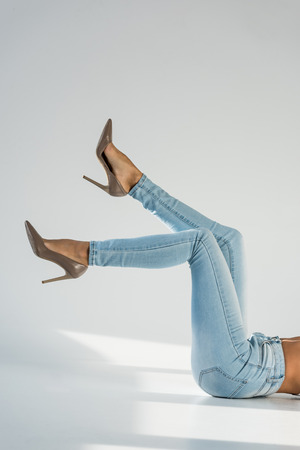Partial view of woman in blue jeans and high-heeled shoes on grey background