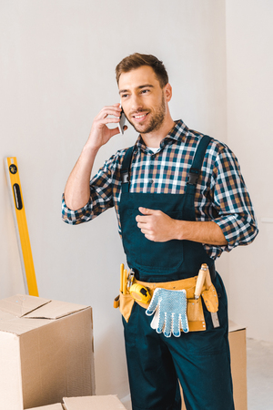 handsome handyman talking on smartphone while standing with tool belt on waist Stock Photo