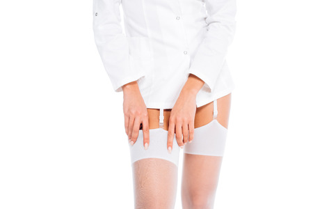 cropped view of nurse in short coat and stockings isolated on white