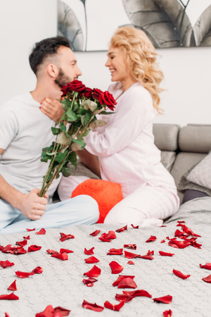 Smiling couple with red roses sitting on bed and looking at each other