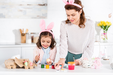 Happy mother and daughter in bunny ears painting easter eggs in kitchen