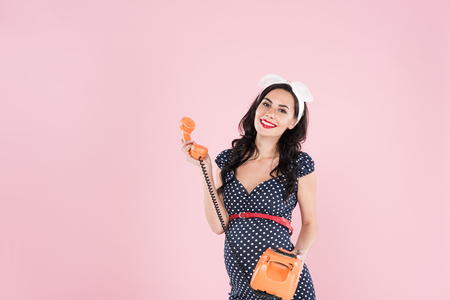 Happy pregnant young woman in dotted dress holding orange telephone isolated on pink