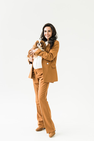 Smiling pregnant woman in brown suit holding dog on white background