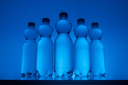 transparent water bottles in row on neon blue background