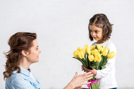 Smiling mother sniffing yellow tulips from daughter isolated on white Imagens
